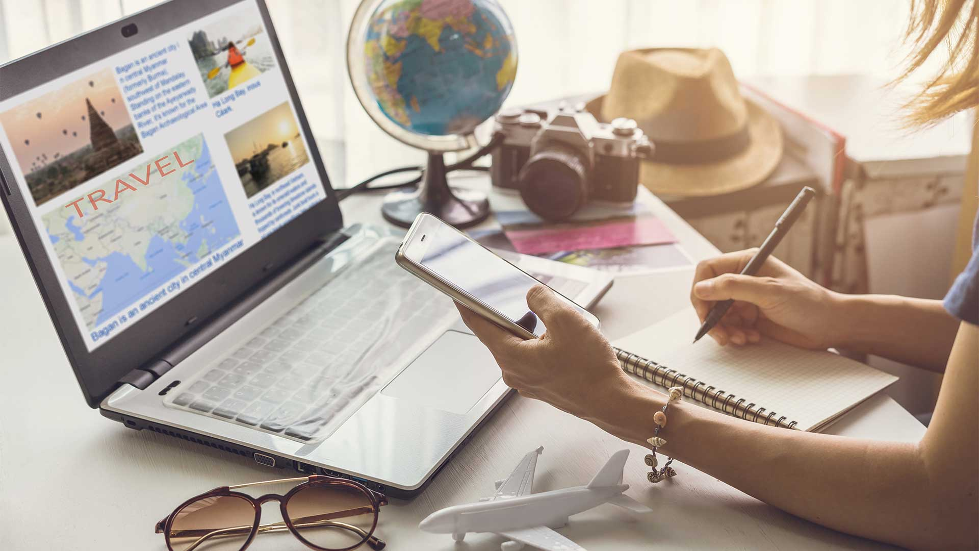 Junge Frau plant ihre Urlaubsreise und recherchiert am Laptop nach Informationen.
