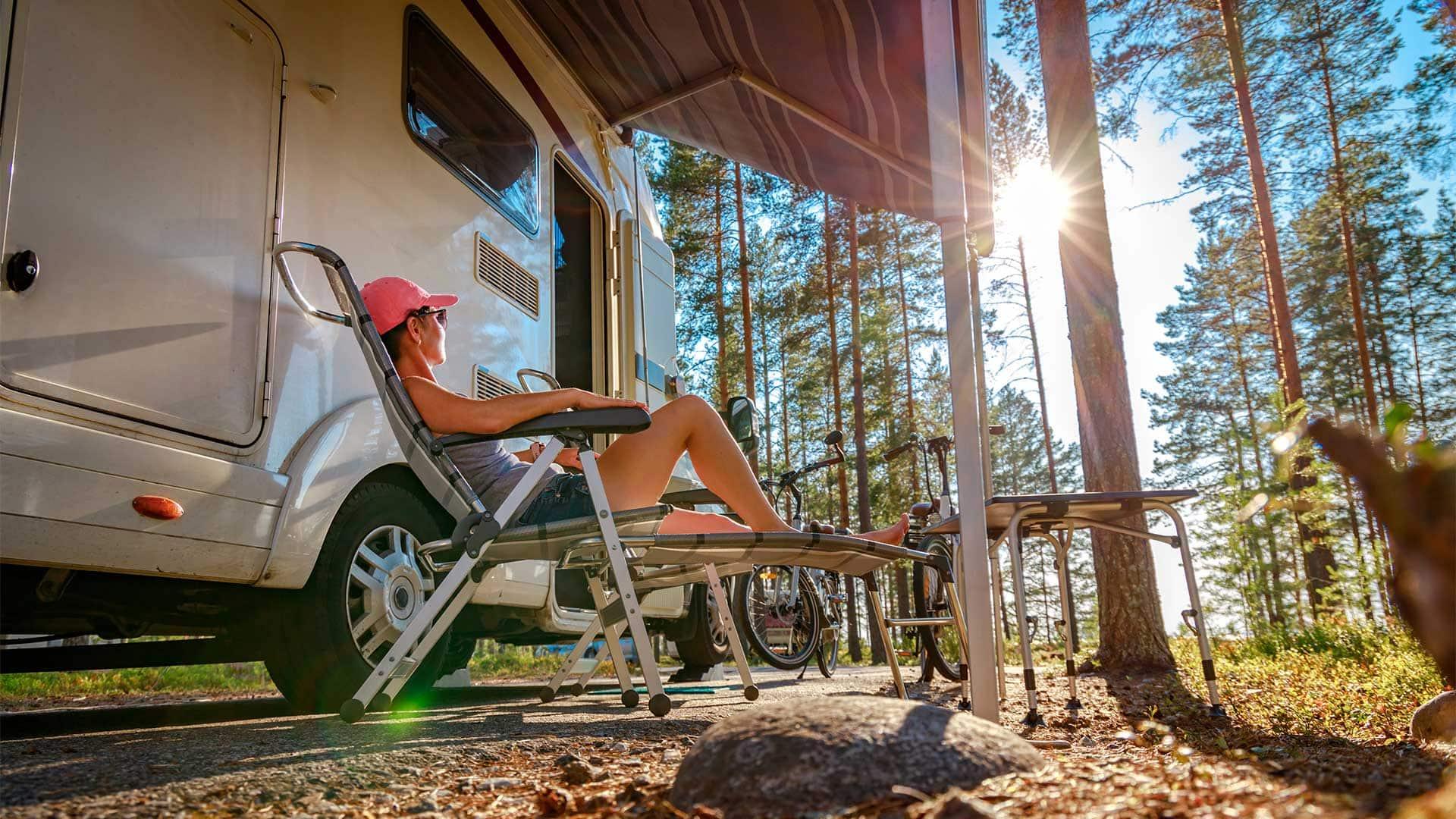 Familienurlaub mit dem Wohnmobil, Ferienreise in der Wohnsiedlung. Frau, die im Campingstuhl vor dem Wohnmobil sitzt.